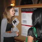 Lauren Mills discusses her Iowa Watch posters with one of a festival judge. Source: Steve Berry
