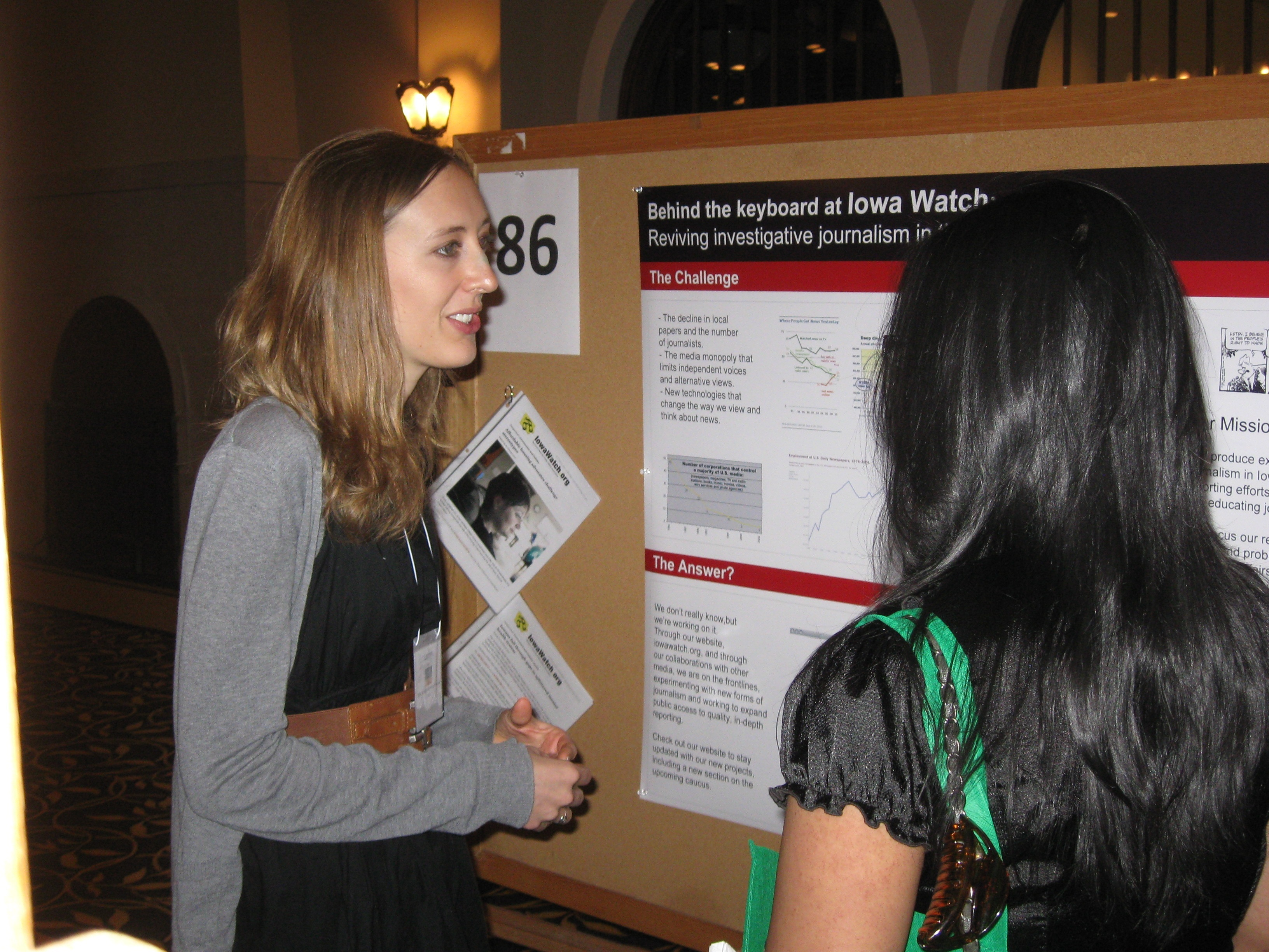 Lauren Mills discusses her Iowa Watch posters with one of a festival judge. Source: Cheryl C. Berry
