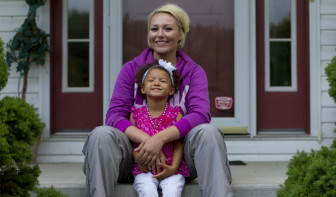 """Army veteran Briana Hawkes, 25, sits with her daughter Aubrey, 3, outside Hawkes' parents' home in Bristolville, Ohio. When Hawkes was deployed, Aubrey """"was trying to reach her hands out to hold me or for me to pick her up and I was like, 'I can't!' It's hard for you to explain something like that to a 1-year-old child,"""" she said. """"But now she's used to it, she understands a lot more."""""""
