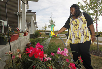 LaTasha Massey waters flowers in her front yard on Sept. 11, in Iowa City. Massey moved into the house in December 2012, participating in a city-run, state-funded program providing down payment assistance to potential home buyers who meet income guidelines.