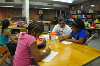 Third graders Jaylynne McDonald (left), Amber Castor and Ayanna Foy work with Belia Hollingsworth during the AFES after-school program in Fort Dodge, Iowa. The kids spend the first 30 minutes working on homework or other projects, then have some STEM training followed by extracurriculars and free time.