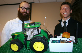 Mitchell Hinrichsen and John Pritchard, students at Iowa State University, pose with a prototype of their tractor rollover device.