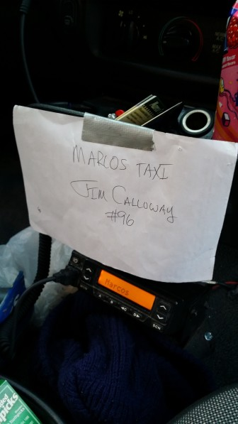 Marcos Taxicab driver Jim Calloway displays a makeshift taxi identification card at the front of a cab he is driving April 7. This is all Iowa City requires for driver identification.