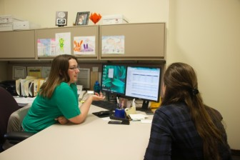 Sara Harrington (left), assistant director of academic progress and loans at the University of Iowa's Office of Student Financial Aid, meets with UI junior Alyssa Lattner on May 1, 2014, to discuss Lattner's financial aid situation.