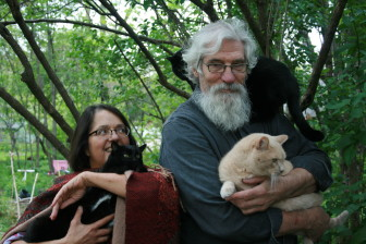 Rebecca Rosenbaum and her husband, Steve Marsden pose with their cats in the backyard of the Iowa City home.