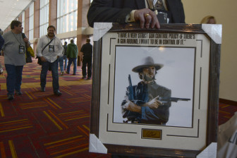 An NRA member carries a framed picture of Clint Eastwood from the exhibit hall at the group's 143rd annual convention.