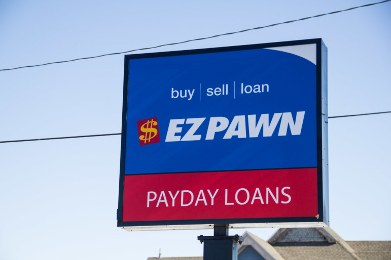 The sign for Easy Cash Solutions and the neighboring store, EZ Pawn, on First Avenue in Cedar Rapids is pictured on February 26.