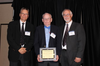 Michael Gartner (center) receives the 2014 Bill Monroe Free Press Champion Award at the annual IowaWatch Celebrating a Free Press and Open Government Banquet. Pictured with Gartner are (left) Bill Monroe and (right) IowaWatch executive director-editor Lyle Muller.