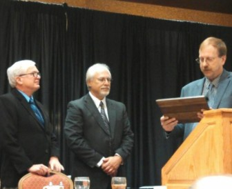IowaWatch co-founder Stephen Berry (left) and executive director-editor Lyle Muller receive the 2014 Excellence in Journalism Award from the Iowa Association for Justice's executive director, Brad Lint, on Nov. 5, 2014, in Des Moines.