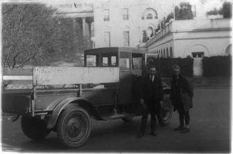 Two men standing next to a Reo truck in 1922.