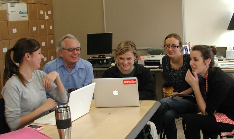 In late 2011, IowaWatch reporters gather around co-founder Stephen Berry discussing stories. Left to right, Emily Hoerner, Berry, Laura Arny, Lauren Mills Shotwell, MacKenzie Elmer.