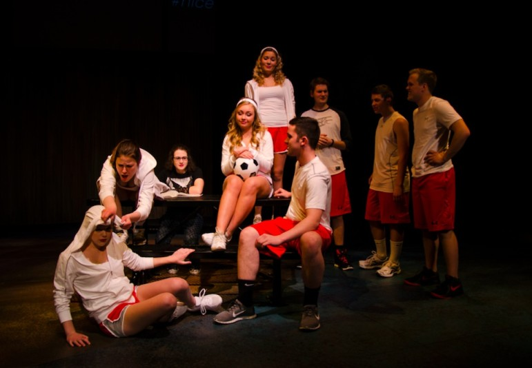 The University of Iowa Theatre Arts Department's cast of the 2015 show Good Kids: Caitlin Edwards-(bottom left), Kylie Jansen (pulling hood over Caitlin's head),  Julia Sears (back of picnic table in black shirt), McKenna Goodman (holding soccer ball), Alex Rinehart (standing on picnic table), Christian Hahn (sitting on picnic table), Kit Grassi, Danny Petersen, Skyler Matthias (standing, left to right).