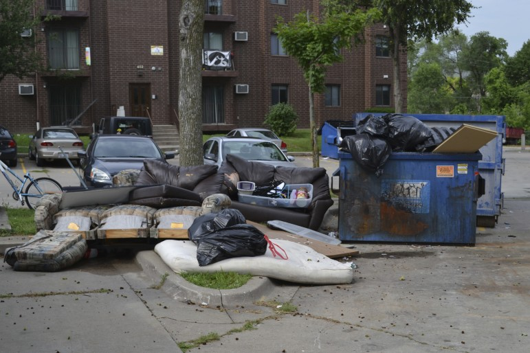 Dumpsters off of Gilbert Street in Iowa City overflow with furniture and trash as University of Iowa students move out on July 28, 2015. Leases for students typically expire July 31 each year.