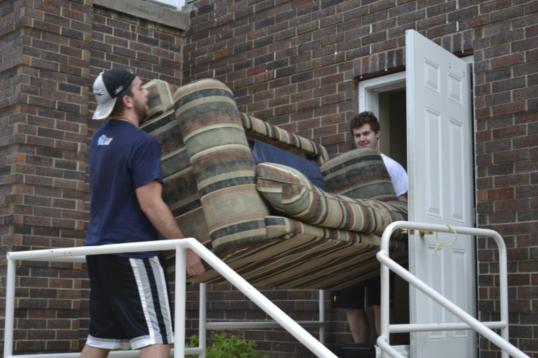 University of Iowa seniors Alec Lombardo, 21, and Steven Moioffer, 20, move furniture out of an apartment on 408 S. Van Buren St. in Iowa City on July 28, 2015. Leases for apartments students typically rent usually expire on July 31 each year.