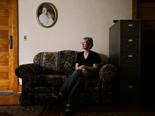 Jody Ewing at her home in Onawa on Thursday, June 25, 2015. Ewing is the founder of Iowa Cold Cases, a website dedicated to cold cases around the state. Originally started as part of a reporting project, Ewing found herself in shock when she had to put her own father, pictured in the portrait above her, on the website after he was killed in an explosion.