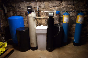 The water filtering system in the basement of Doug and Dawn Reeves' home near Stoughton, Wis., shows the efforts the couple has made to remove atrazine and other contaminants from their drinking water. That includes two small blue tanks that remove sediments, the black tank that removes nitrate, and two large blue tanks to remove volatile organic compounds, herbicides and pesticides. The large blue filters cost the Reeves family $1,500 a piece. There also is a reverse osmosis filter attached to the kitchen faucet.