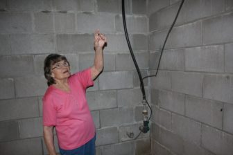 Joan Michels, of Earling, Iowa, points to the water lines coming in her house from the well outside. Michels said she didn't know the exact age of the well, but it was there since at least the 1950s. Her husband first brought the water lines into the house in the 60s, before that the house had no running water. Photo taken Aug. 19, 2016.